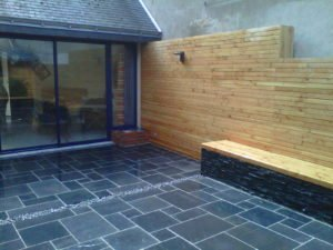 Terrasse en carrelage avec séparation décorative en graviers, un mur et banc en bois et une baie vitrée par Aux 1001 Saisons