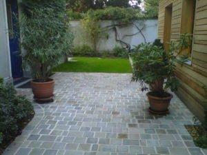 Aménagement extérieur avec des plantes en pot et une allée en dalles par Aux 1001 Saisons