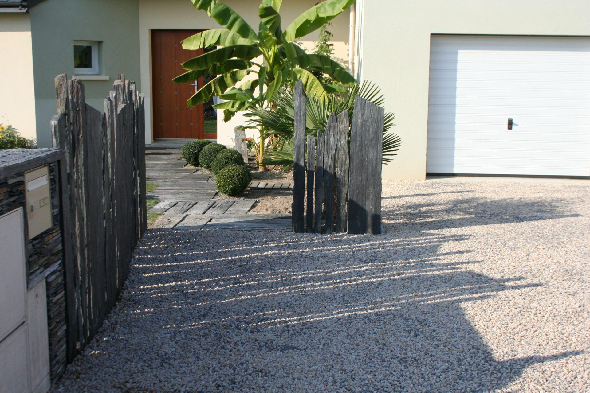 Aménagement d'une allée devant une maison avec des graviers, des paravents en pierres et des dalles devant la porte d'entrée par Aux 1001 Saisons